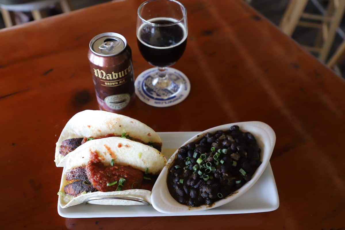 Fish tacos with black beans on side and a beer can and glass on wood table.