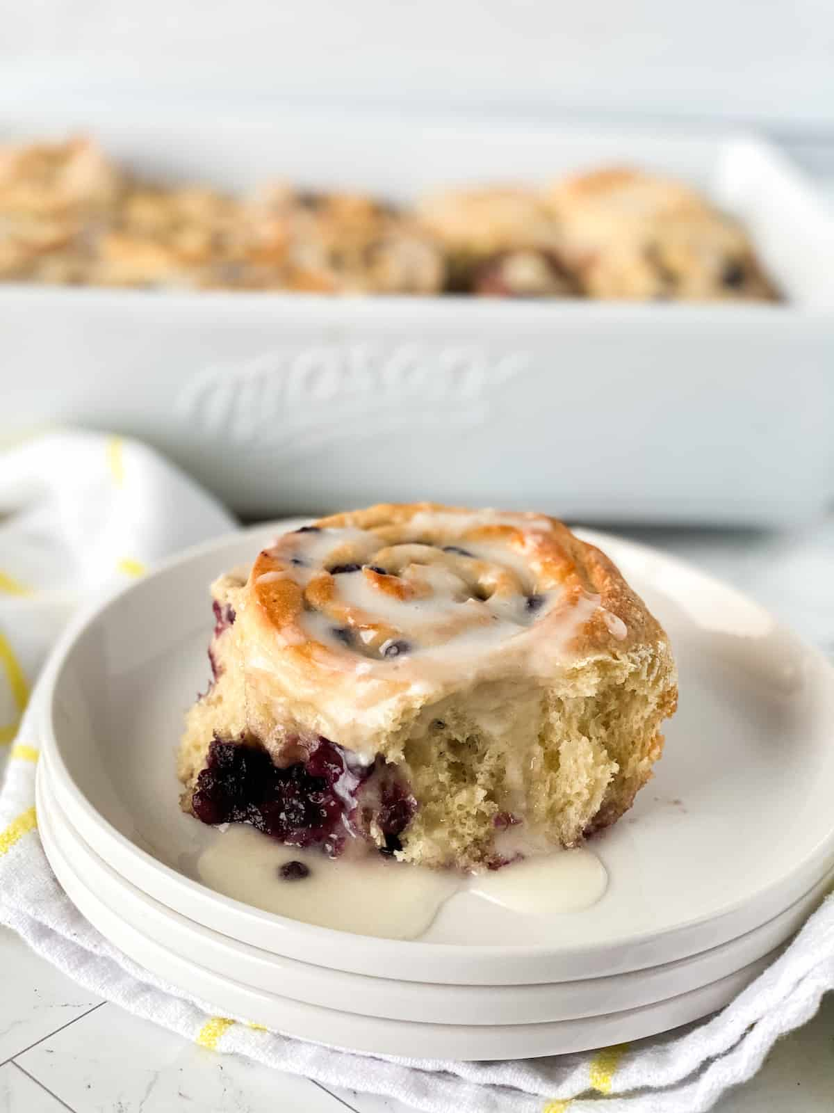Blueberry sweet buns with white icing on off white plate