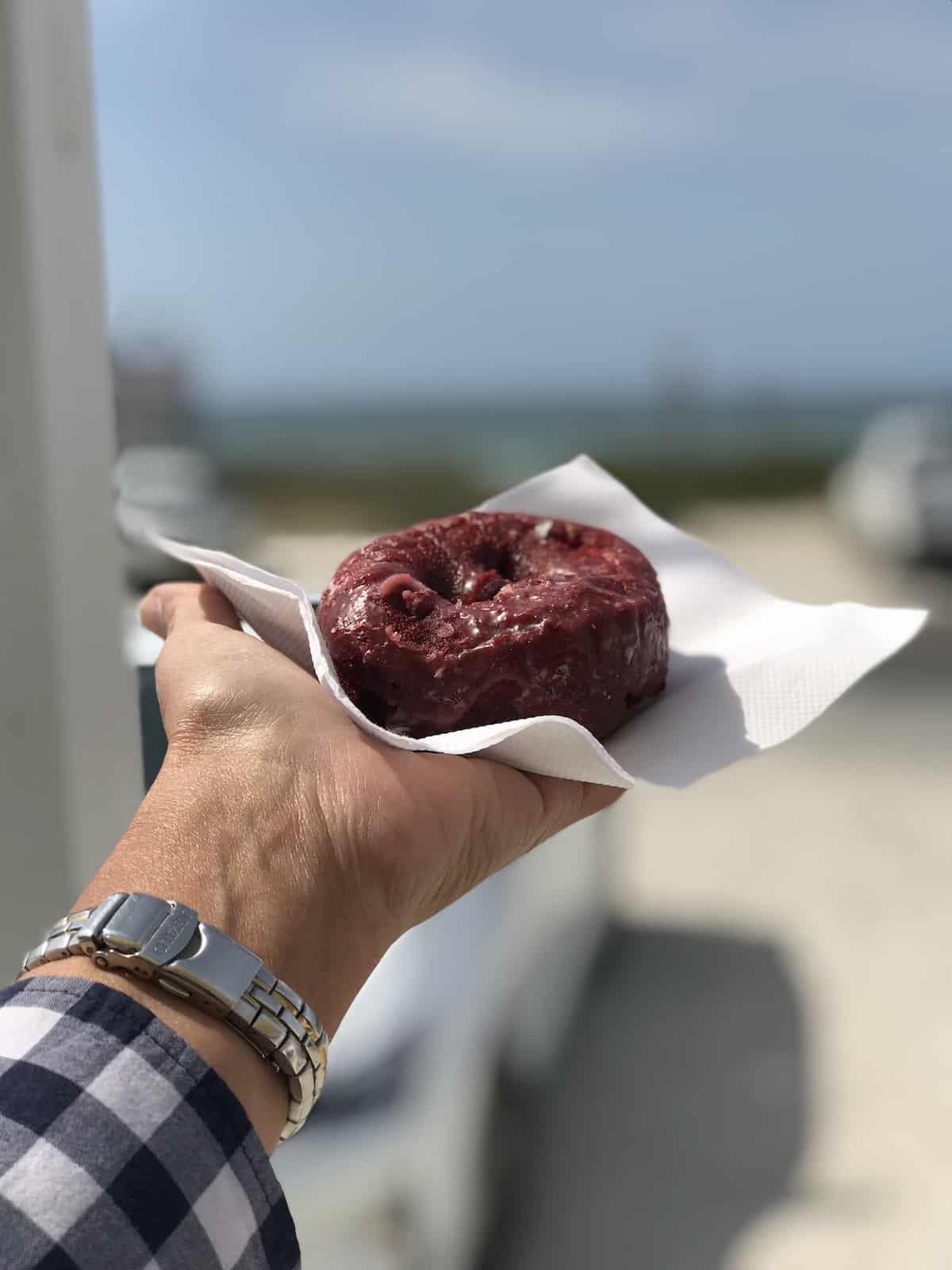 Red velvet doughnut with beach in background.