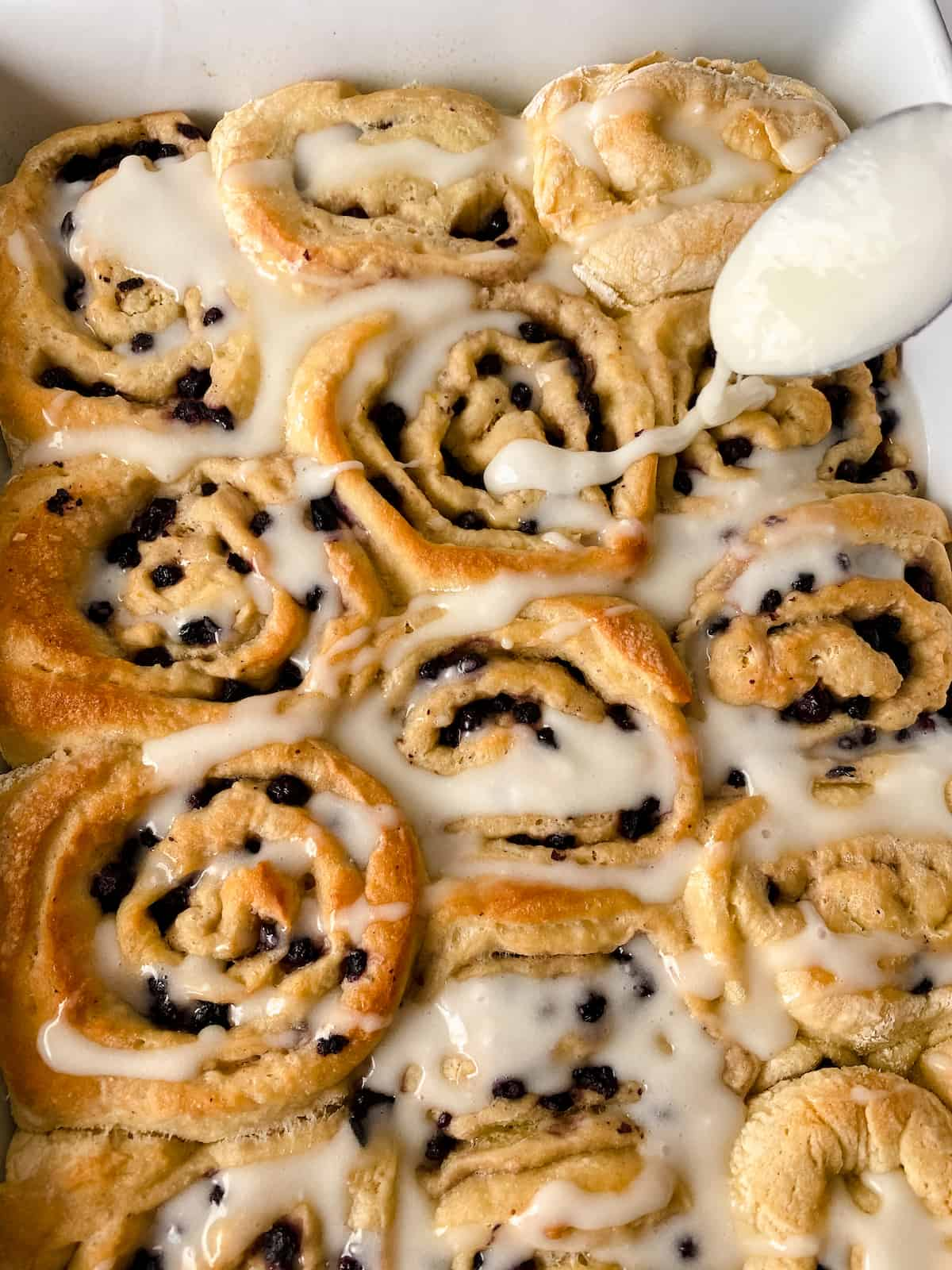 Icing blueberry sweet buns in white pan.
