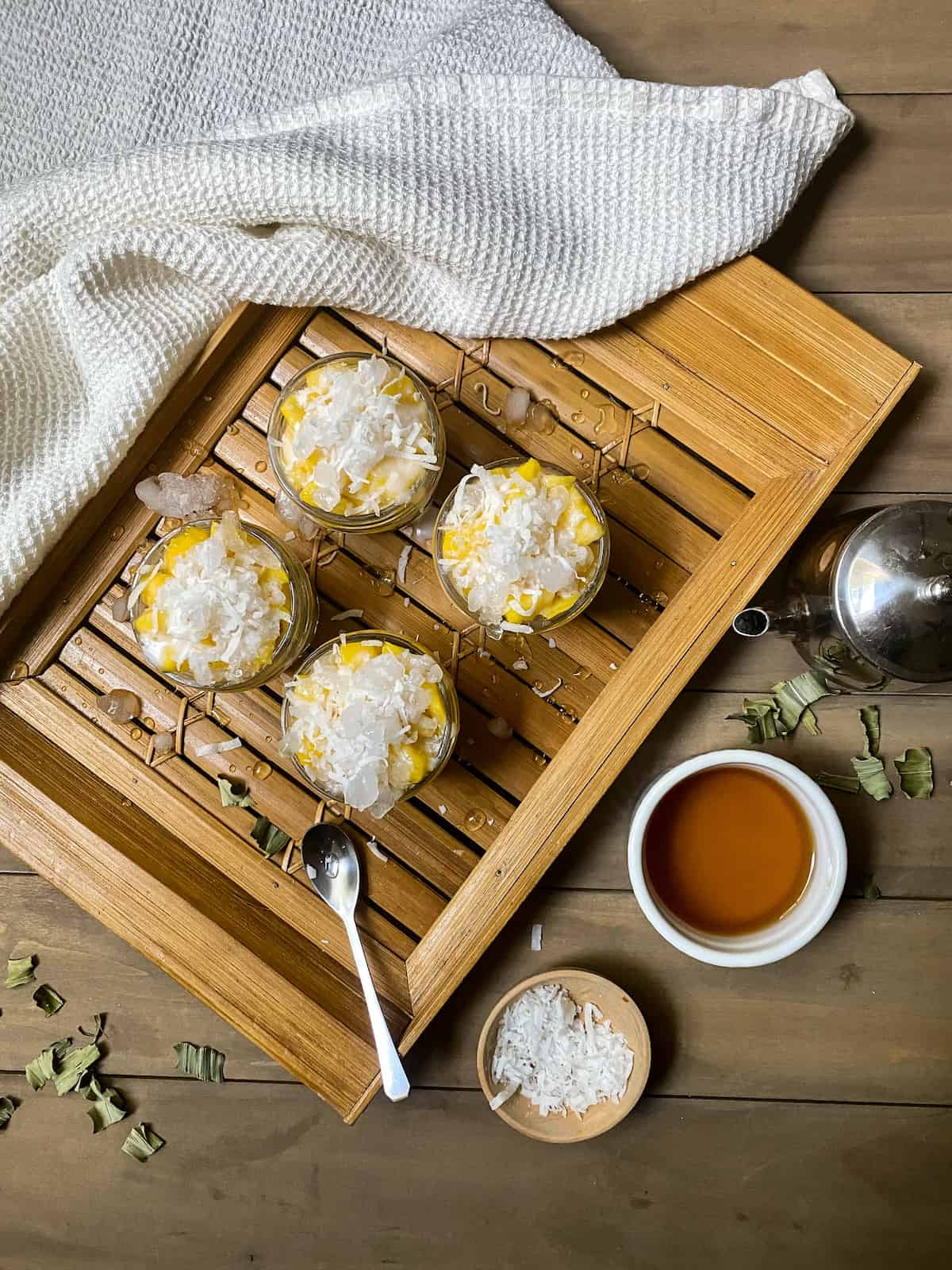 Mango with coconut in a jar topped with crushed ice on a bamboo board with a white cloth and other ingredients.