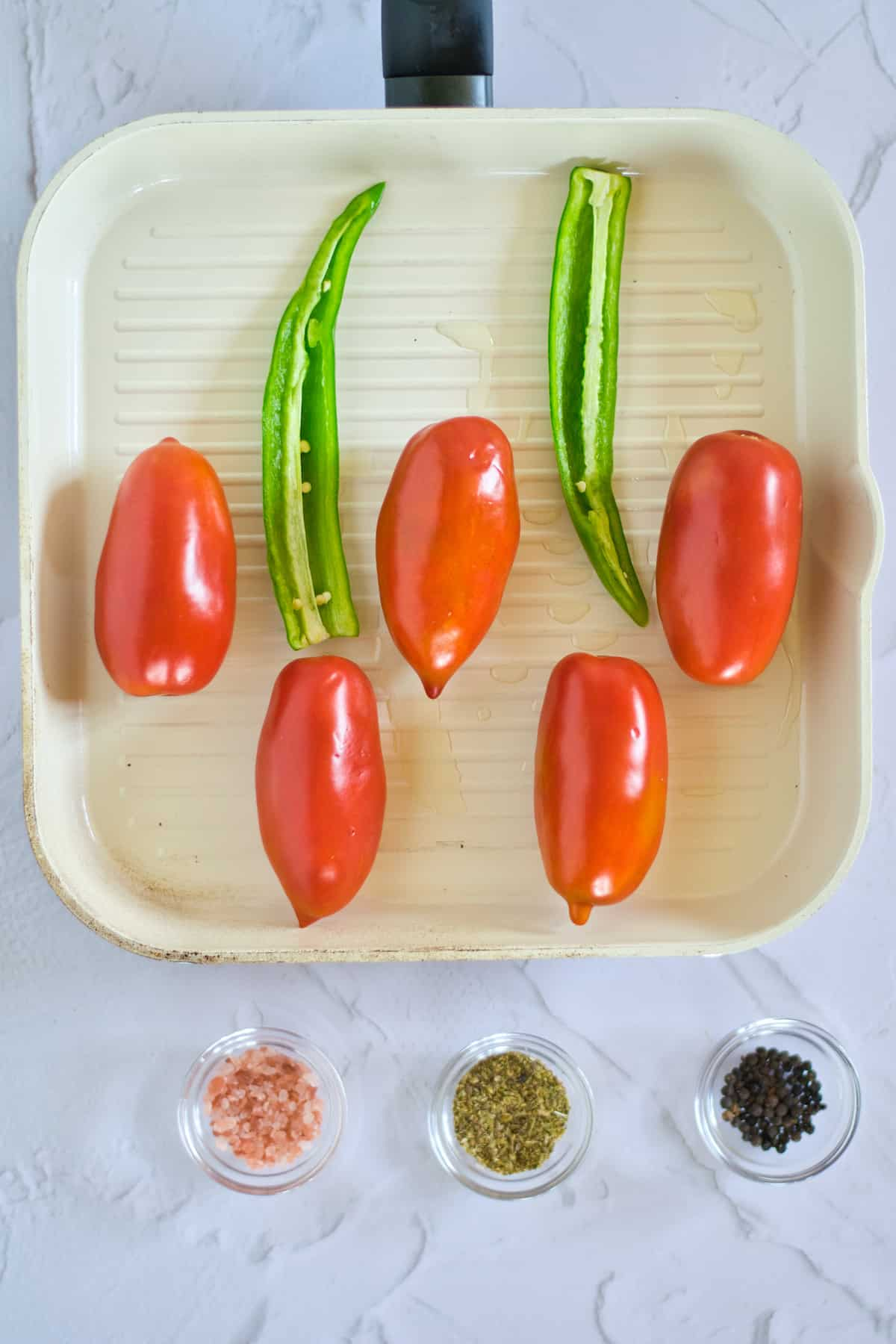 Tomatoes and Serrano peppers in pan with olive oil.