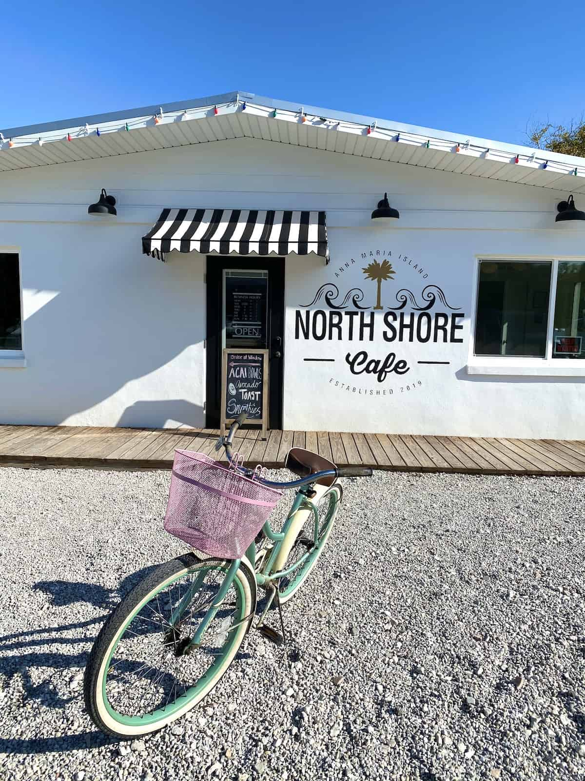 Front of North Shore Cafe with bicycle in parking lot.