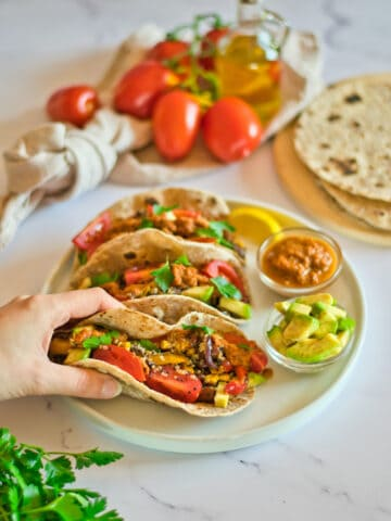 Quinoa tacos on a plate with hand holding one.