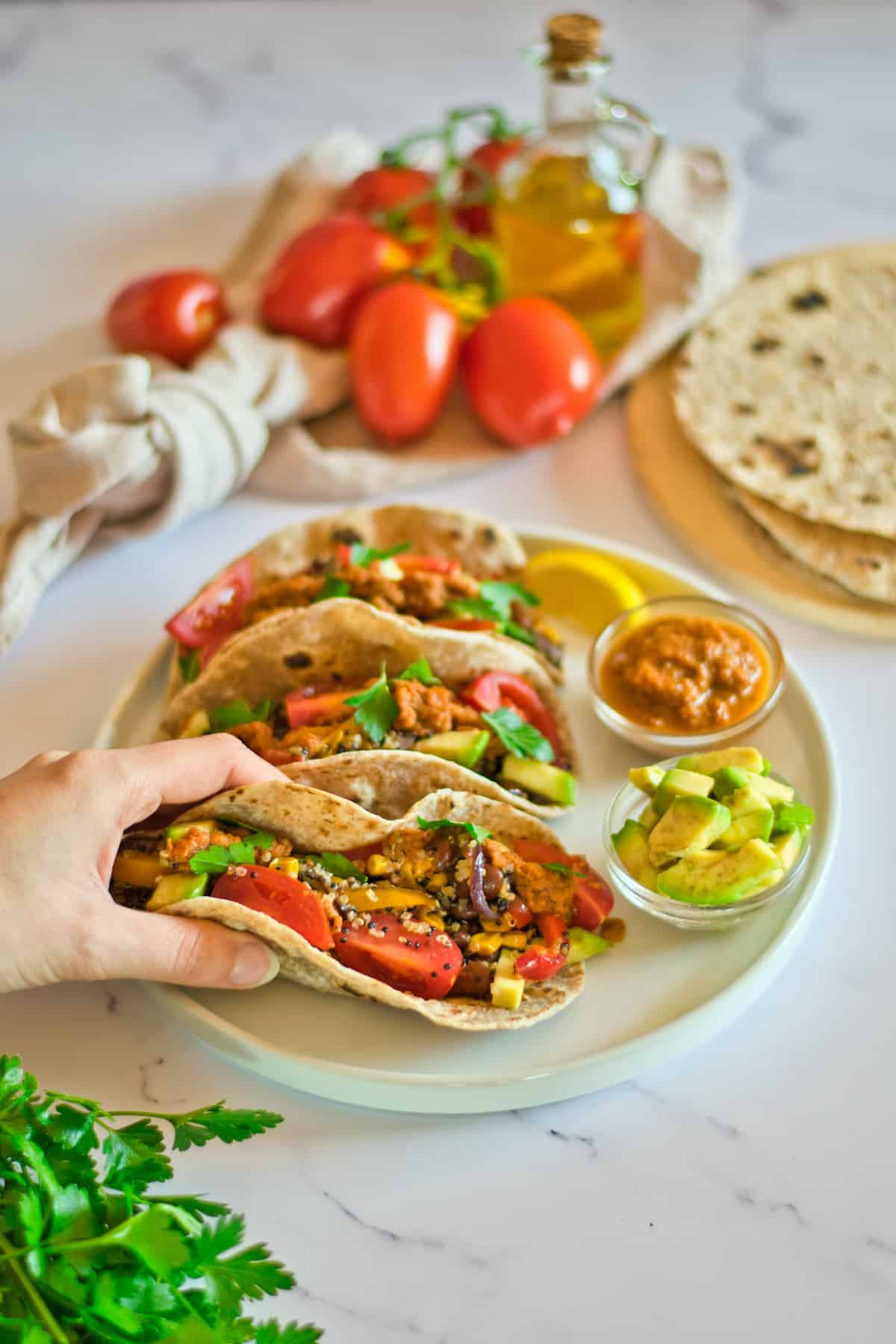 Hand holding a Quinoa Taco with more tacos and ingredients in the background