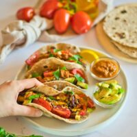 Hand holding a quinoa taco with more tacos and ingredients in background.