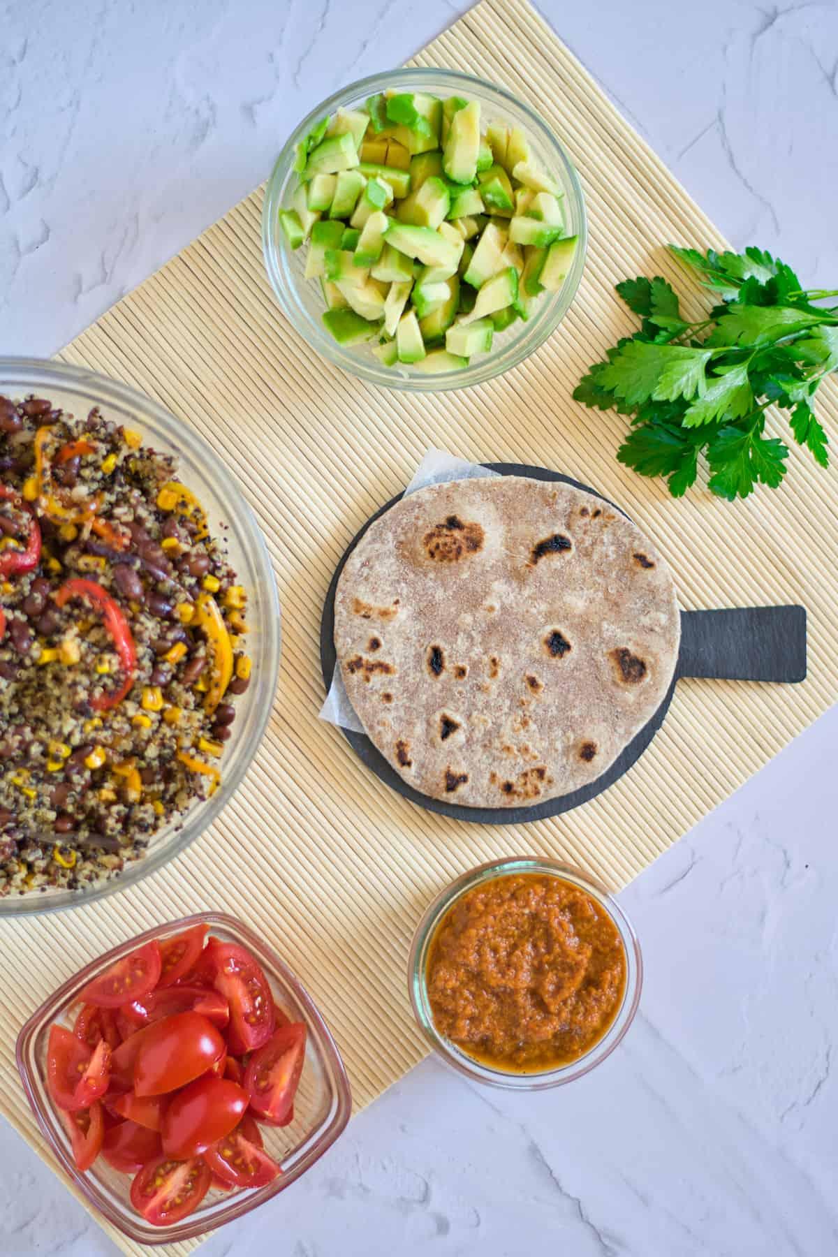 Avocado, quinoa mix, tortilla, salsa, tomatoes on a mat.