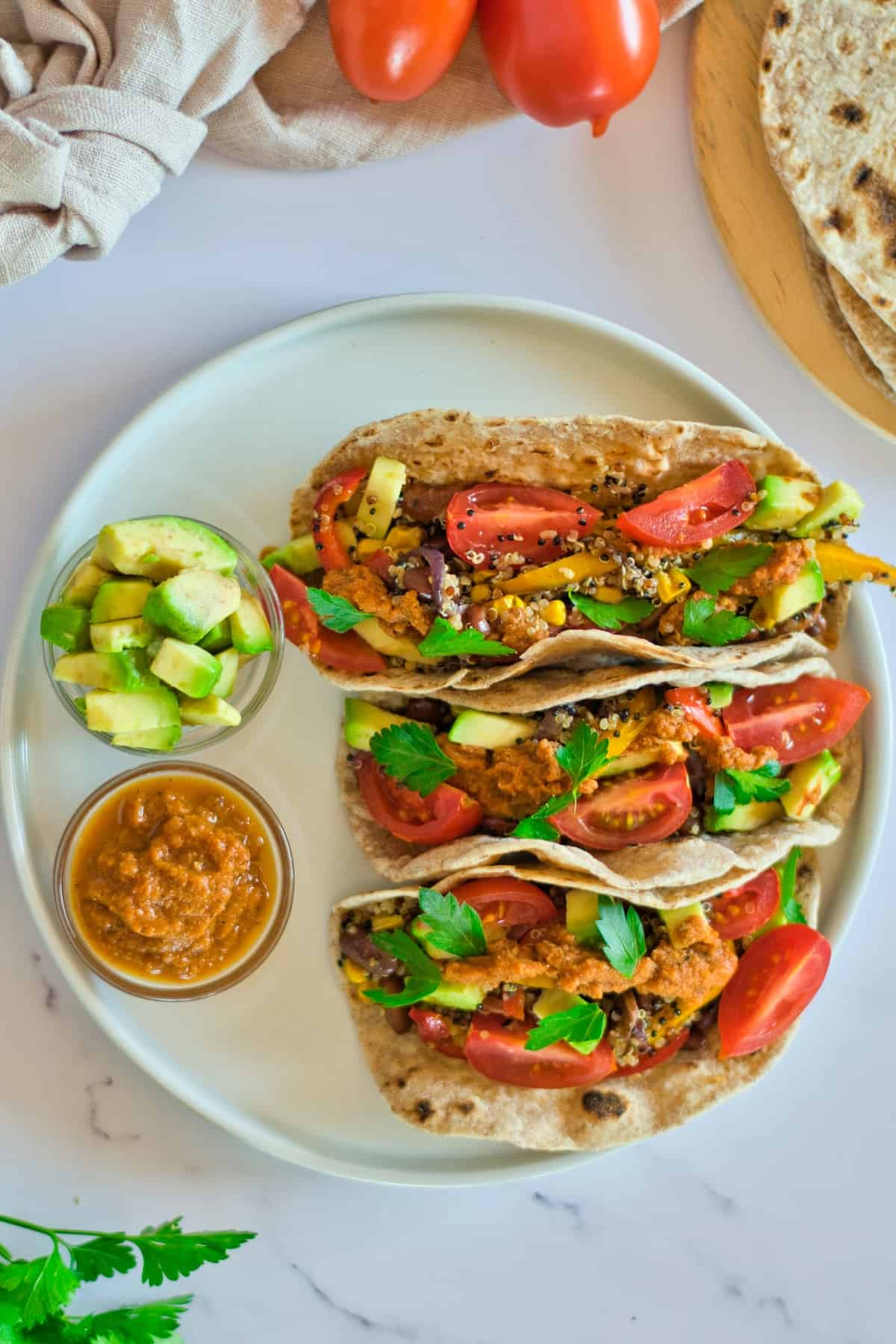 3 quinoa tacos on white plate with side of avocado and salsa.