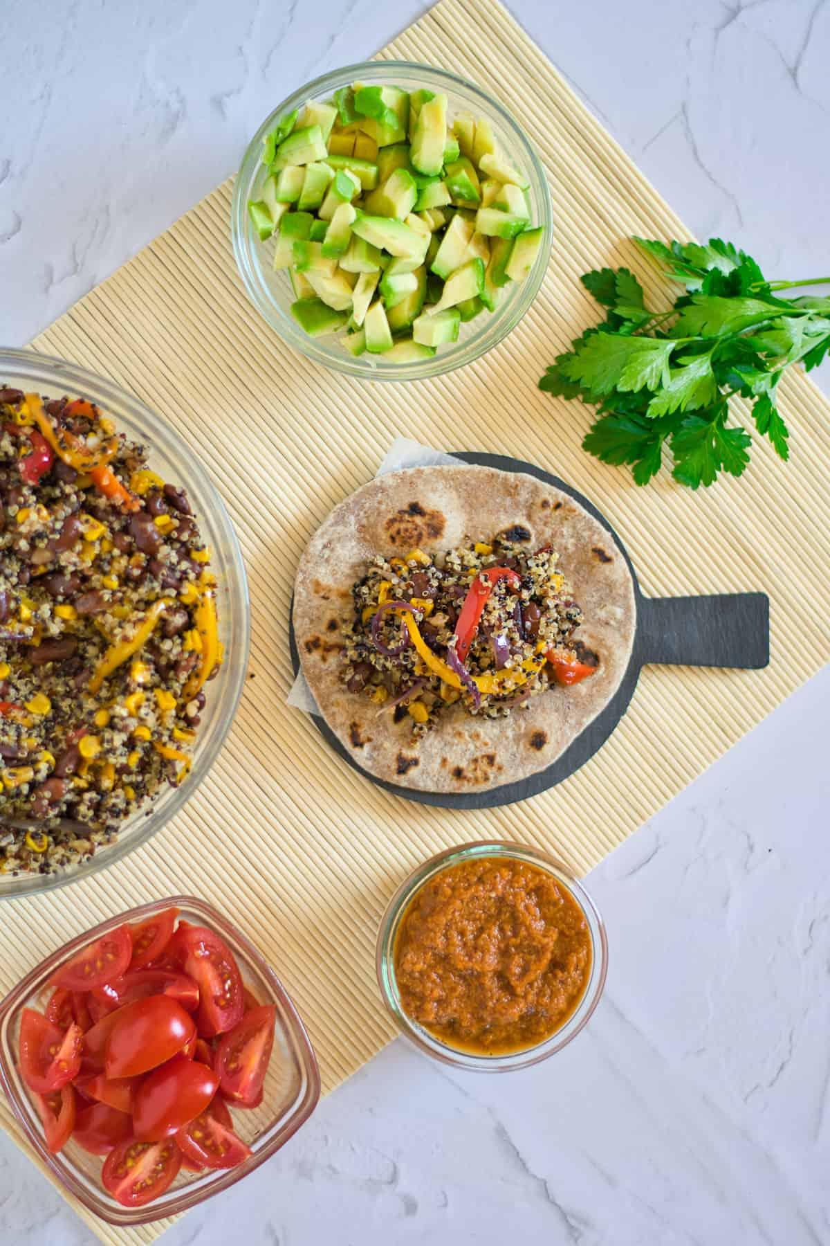 Avocado, tortilla mix. quinoa taco on mat with cilantro, salsa, tomatoes.