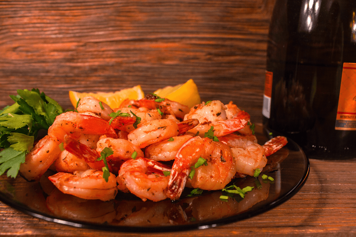 Shrimp with lemon and parsley with wine bottle in background.
