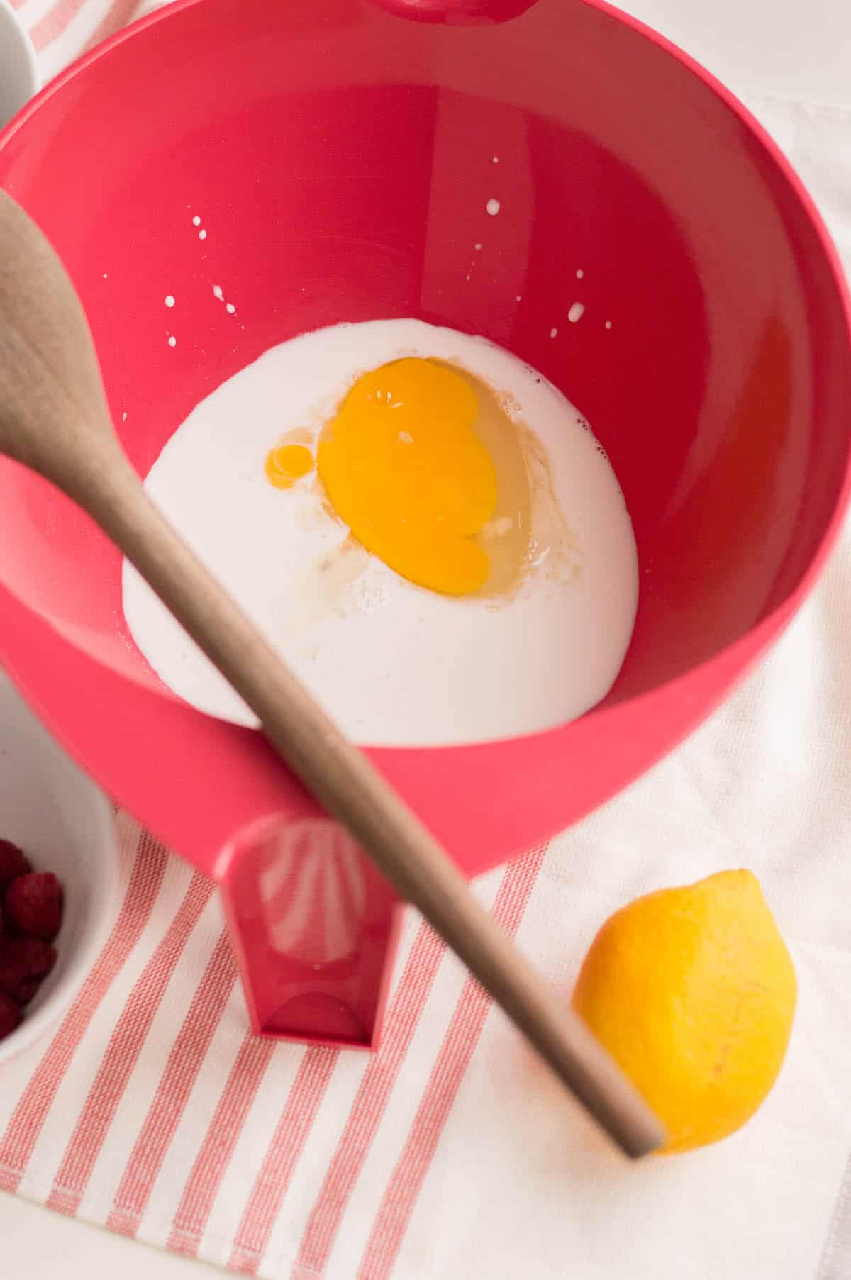 Egg and milk in red bowl on striped dishtowel.