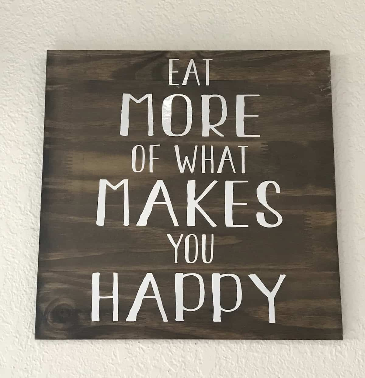 Sign on wall in The Yard restaurant, Eat More of What Makes You Happy
