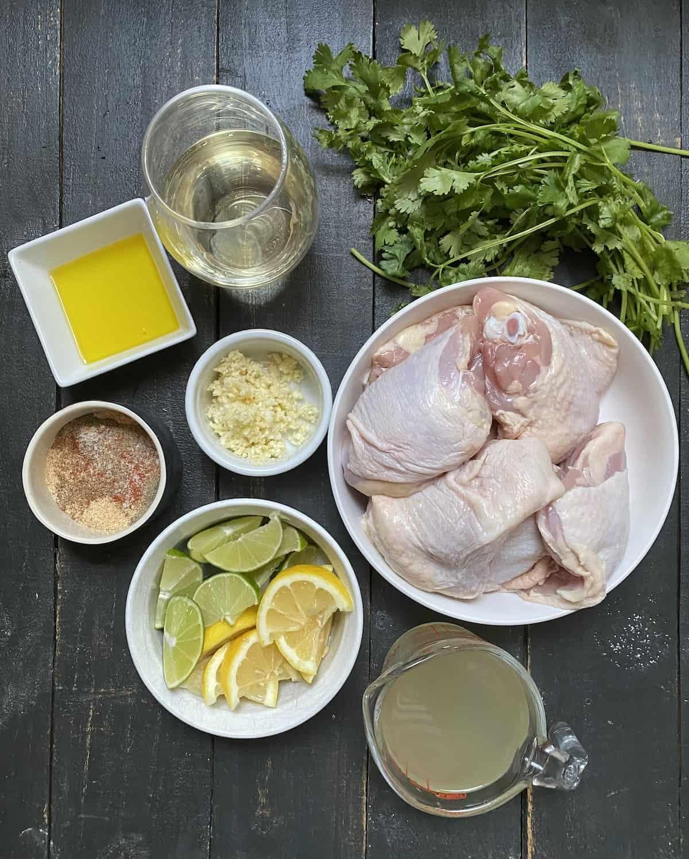 Raw chicken, lemons, limes, seasoning garlic, chicken broth, cilantro, and wine on a black table.