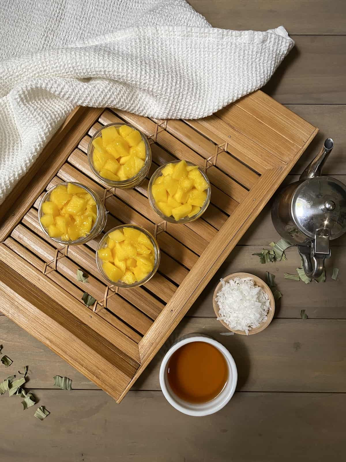 Mango on a bamboo board with a white cloth and other ingredients.