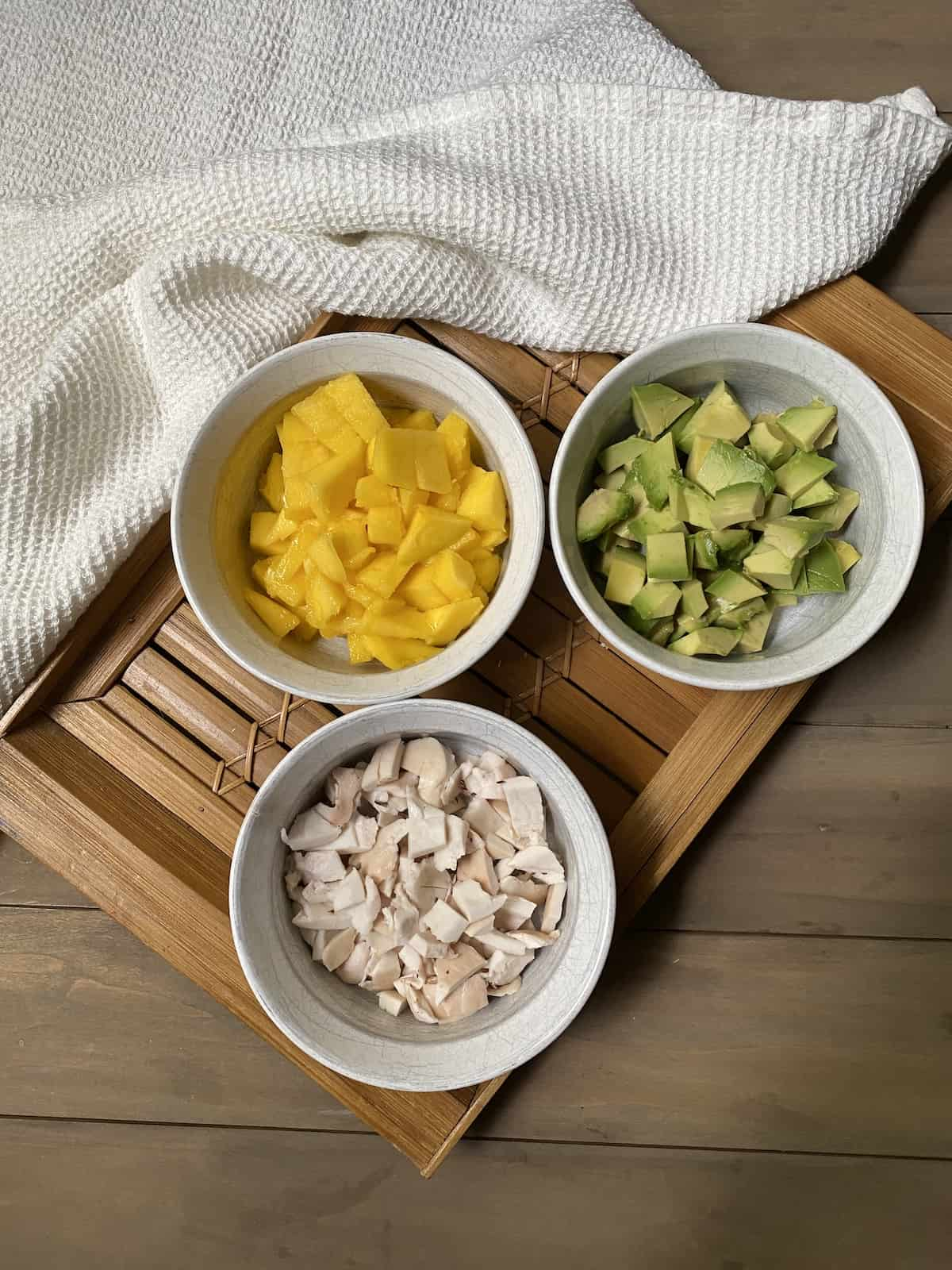 Mango, avocado, and young coconut in white dishes on a bamboo tray.