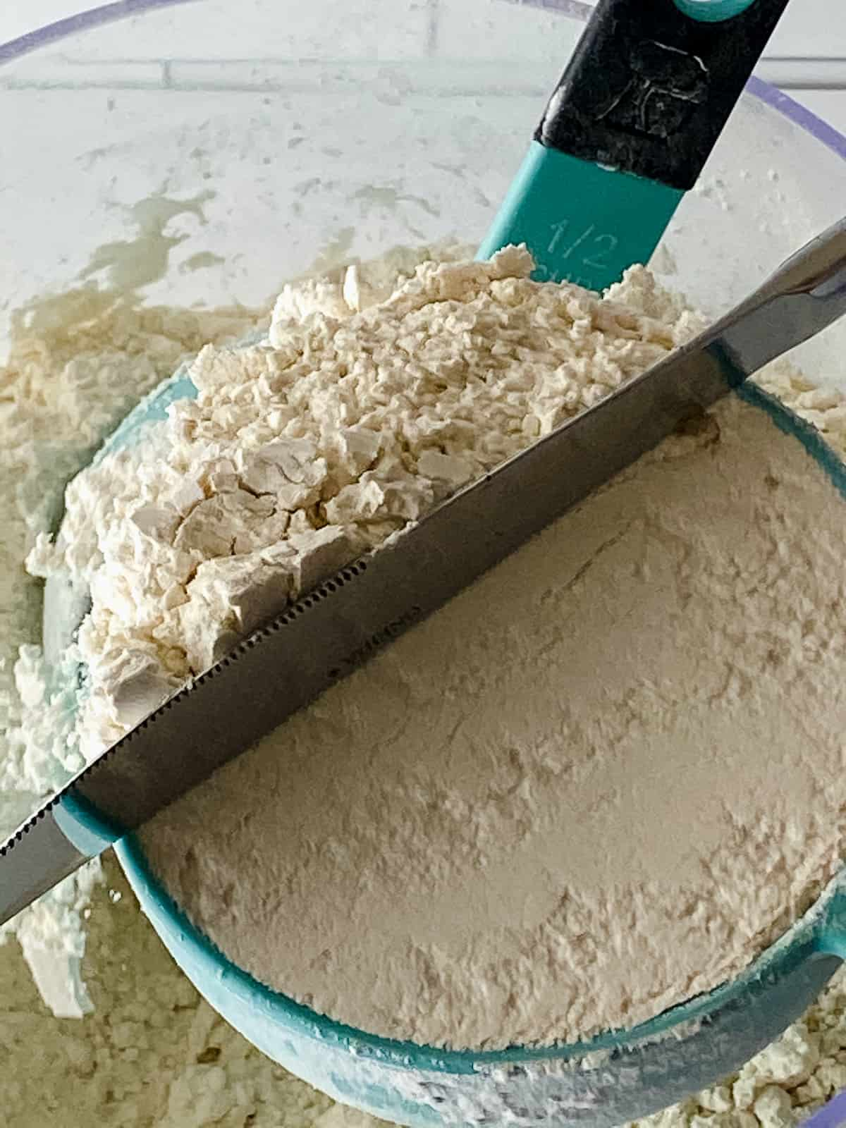 Measuring flour in a cup and leveling with a knife