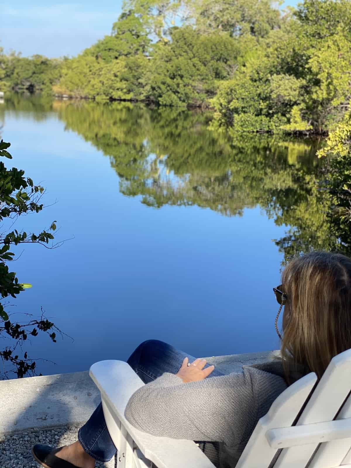 Woman sitting in white chair looking over river.