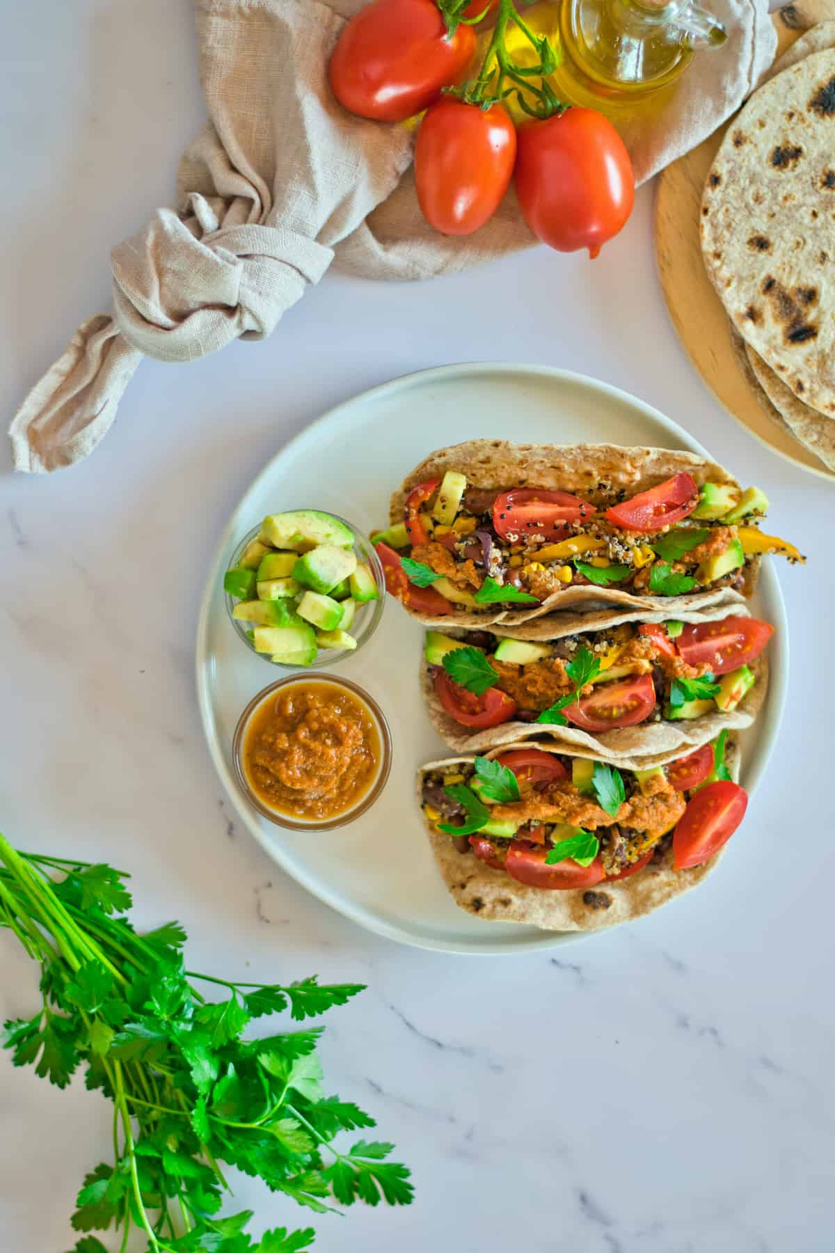 Quinoa tacos on a white plate on a marble table with cilantro, tomatoes, and tortillas.