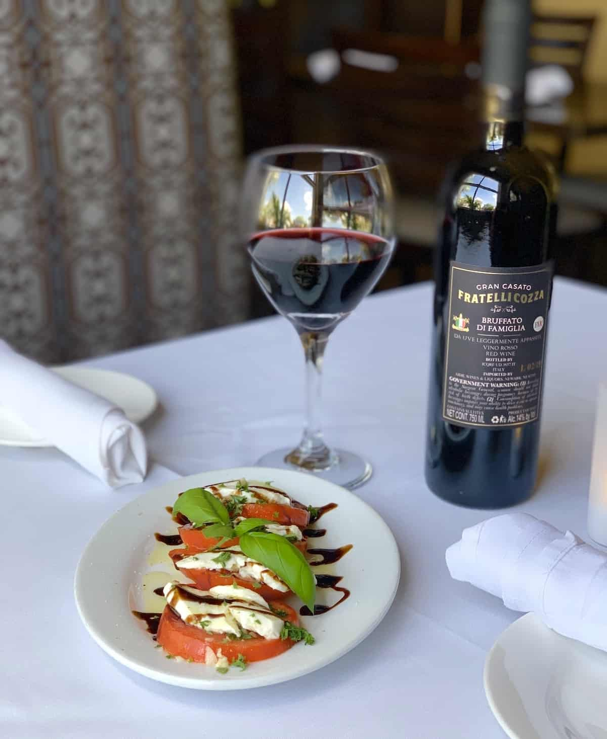 Tomato and mozzarella salad with a glass and bottle of wine in background.