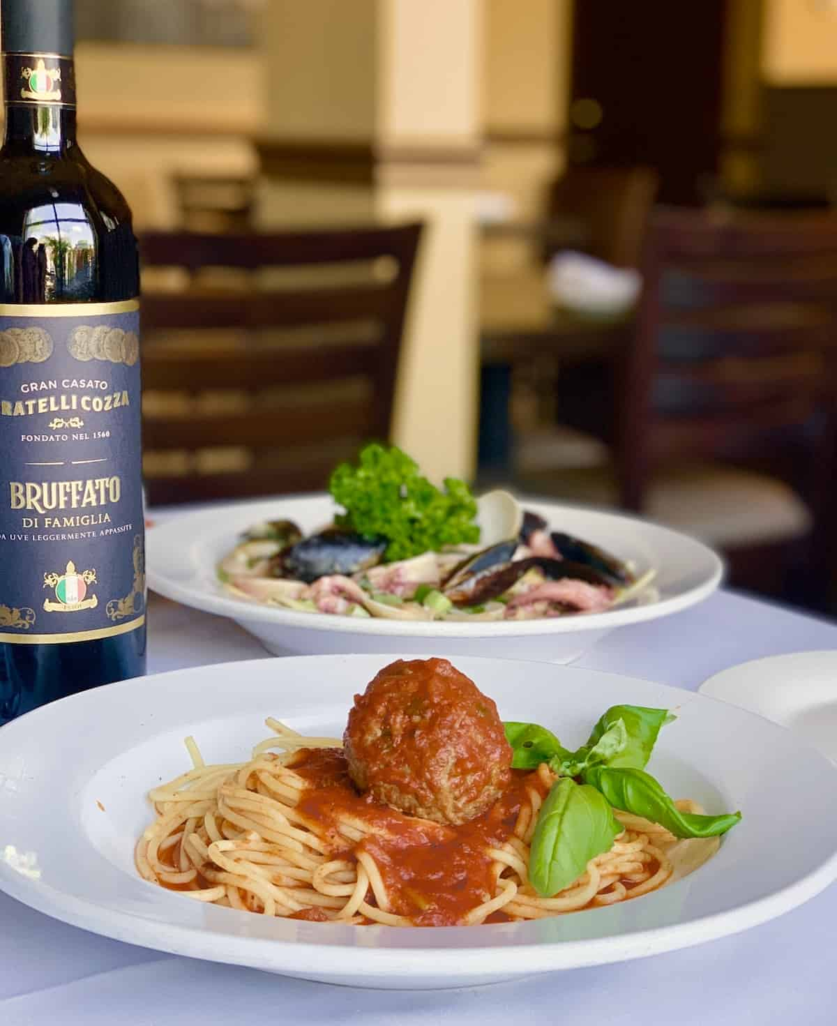 Spaghetti and meatballs, bottle of wine, seafood dish in background, all on white tabelcoth.