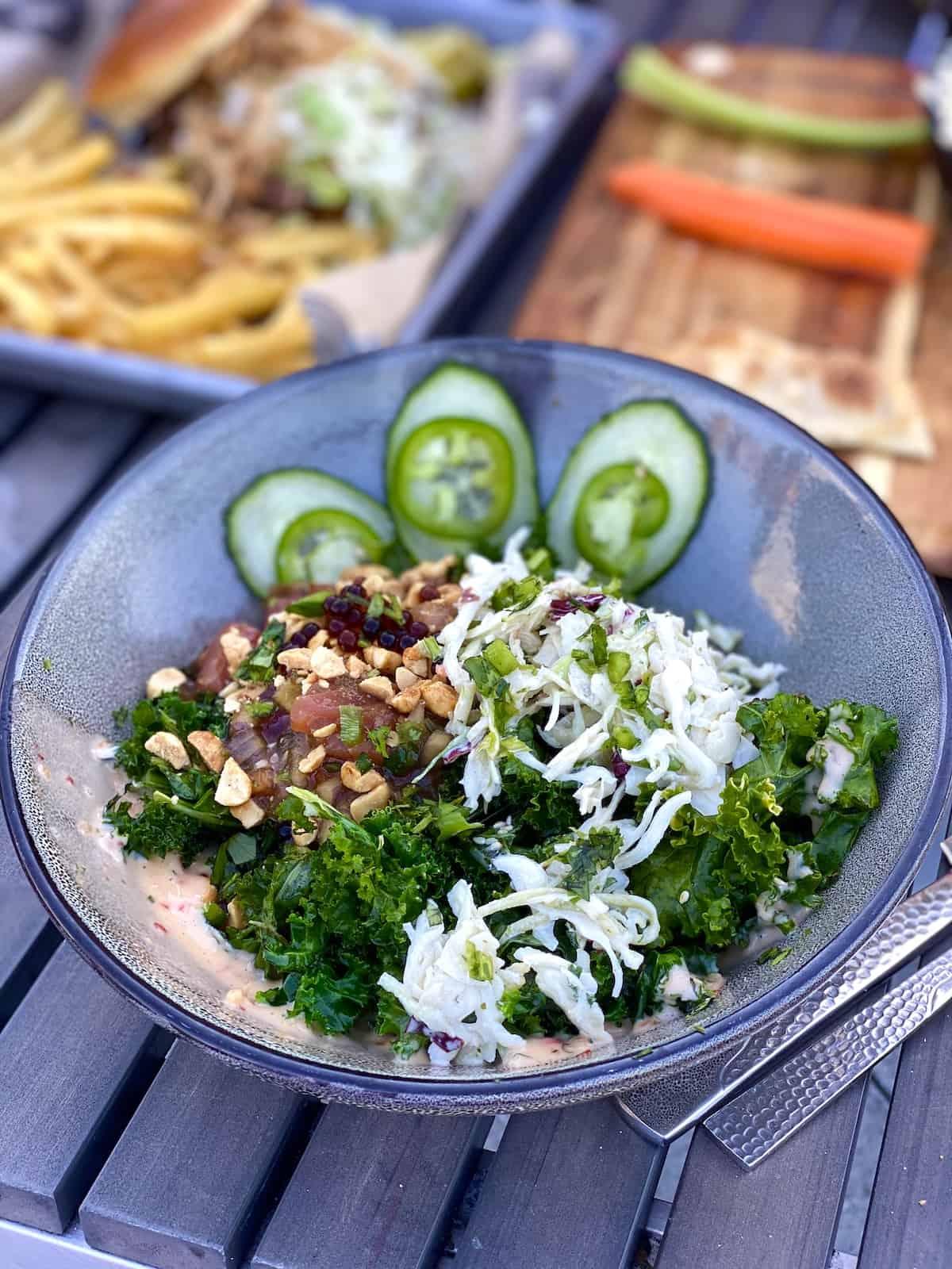 Fresh raw tuna and kale salad with veggies and nuts.