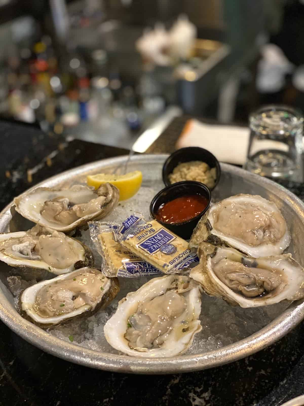 Oysters, cocktail sauce, and crackers on a tray of ice.