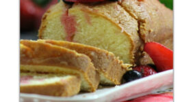 Pound cake with berries and mint in a white plate on a red plaid tablecloth.