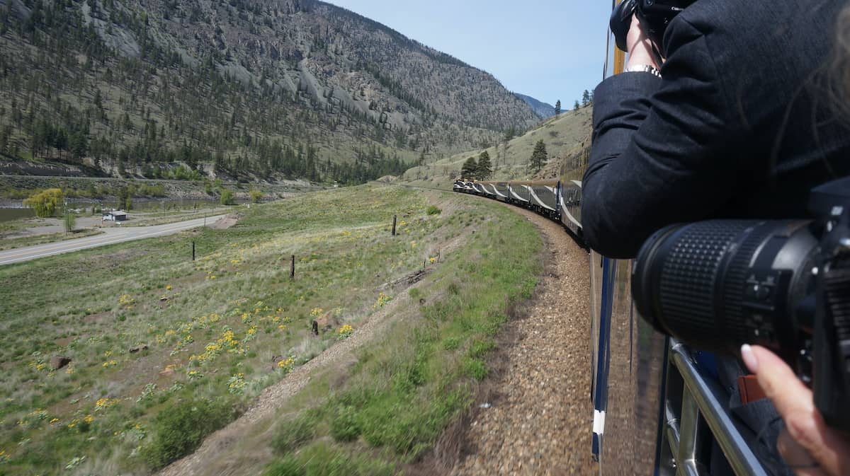 People with cameras taking photos of landscape on train.