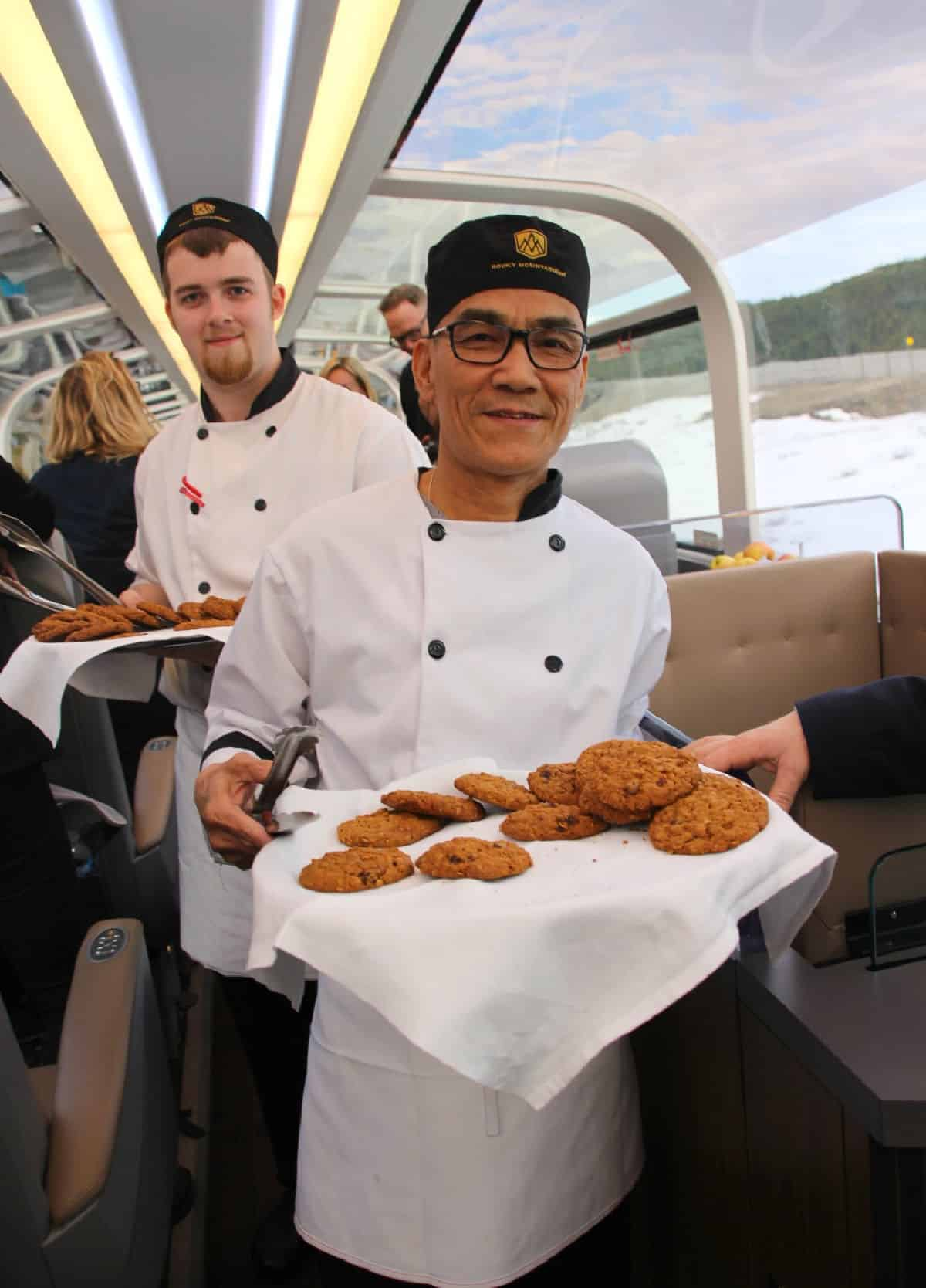 Men serving cookies on a train.