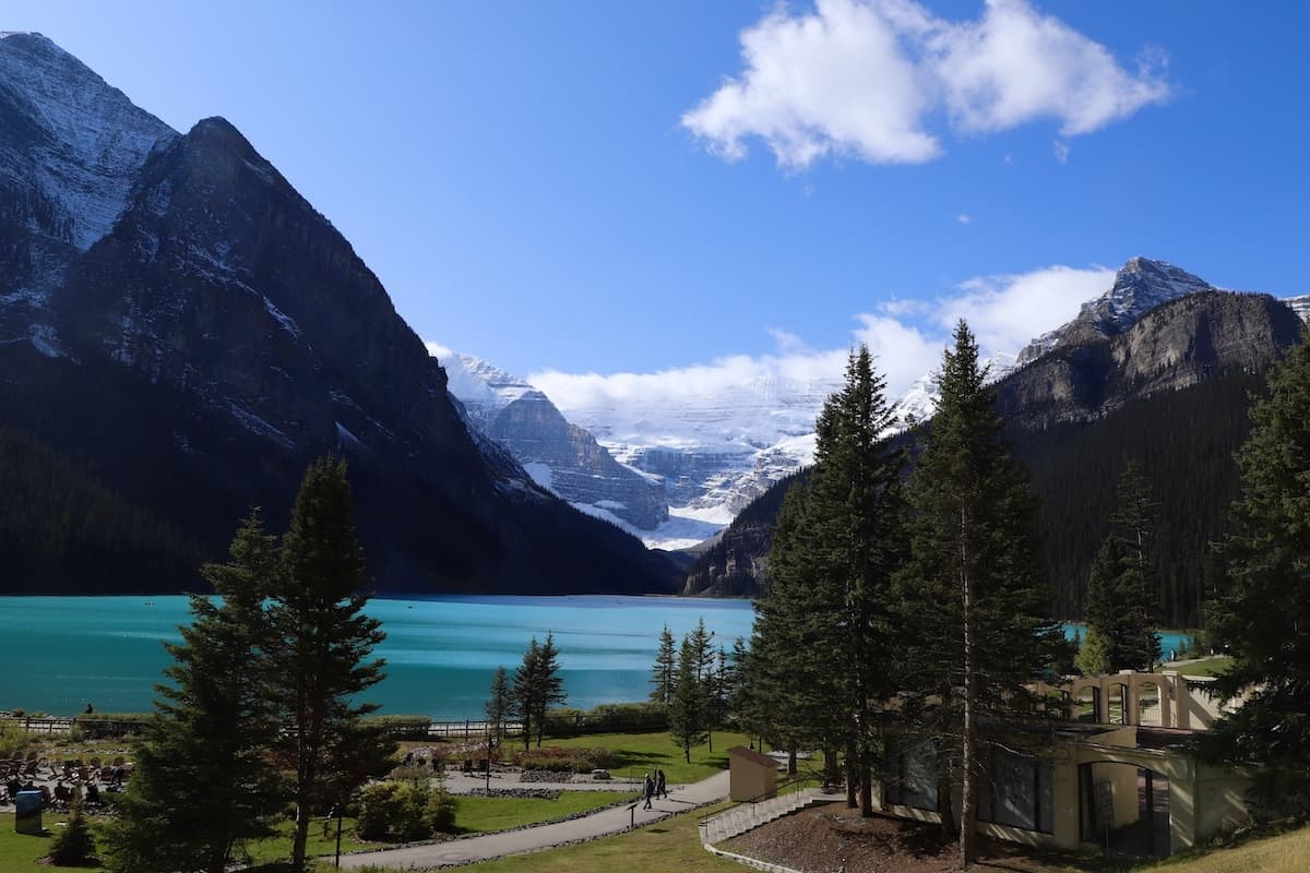 Blue lake surrounded by pine trees and blue sky with mountains in background.
