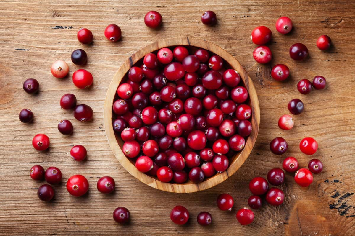 Wooden bowl filled with fresh cranberries on a wood counter.