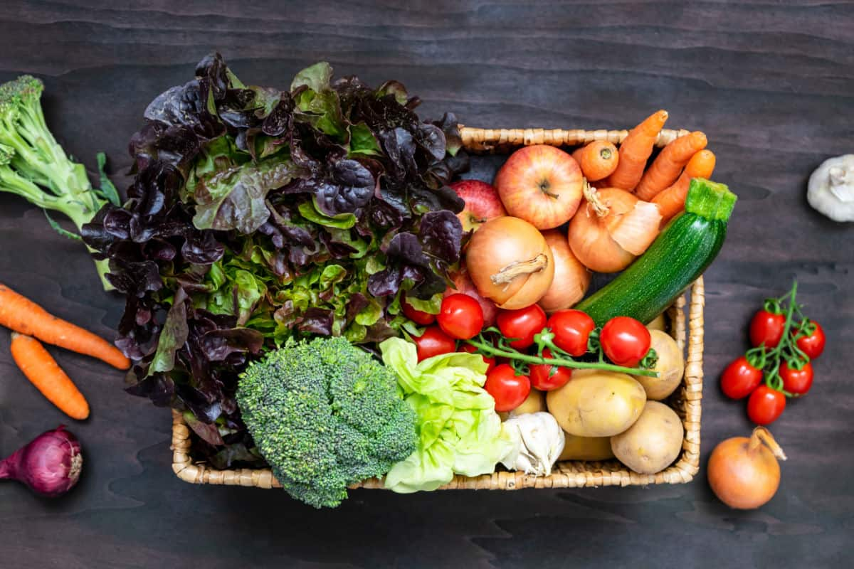 Rectangular wicker basket full of vegetables with cherry tomatoes, onion, carrots, garlic, and red onion on table.