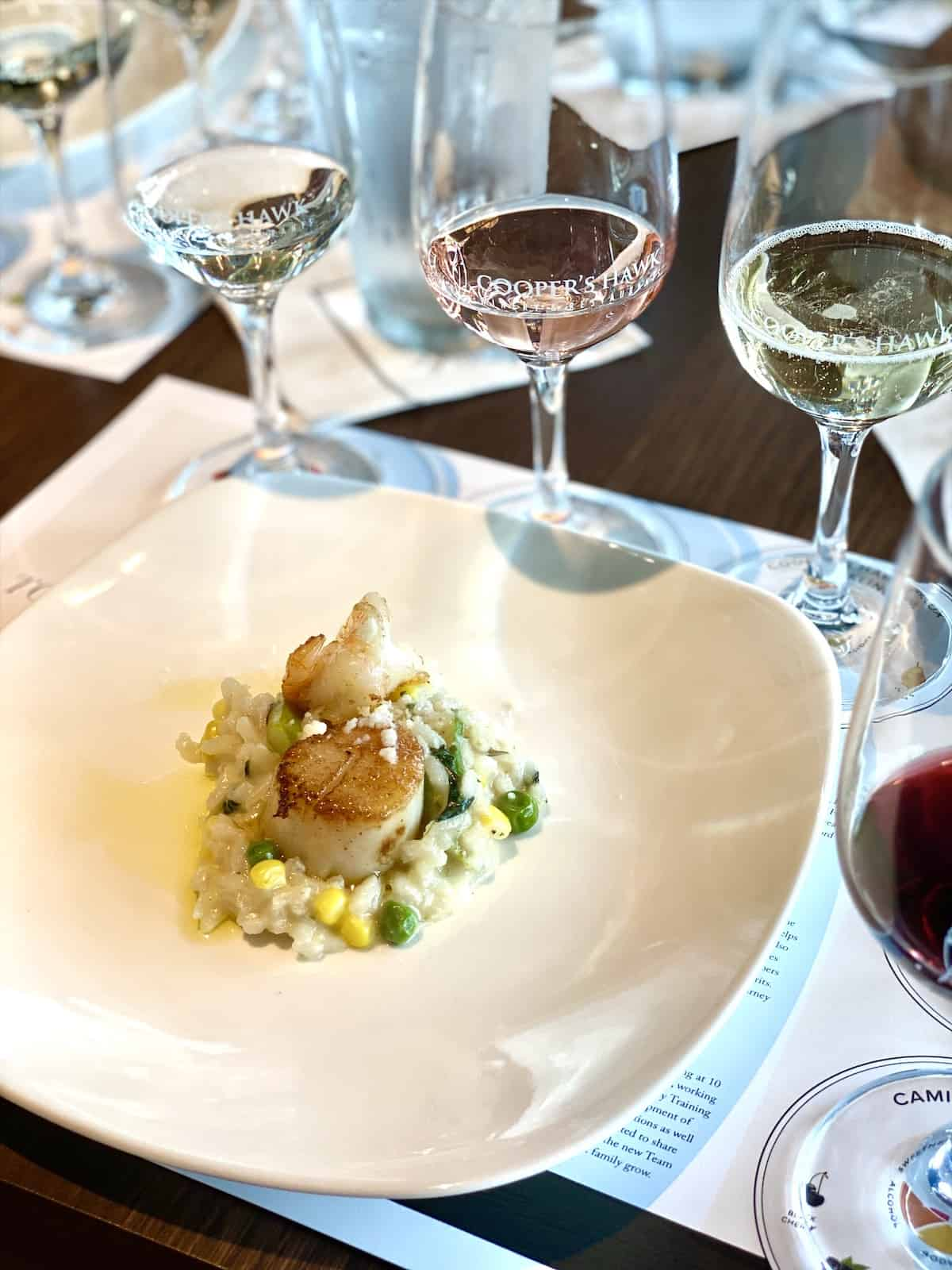 Scallops and risotto with wine glasses in background.