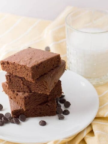 Dark chocolate brownies on a white plate on a yellow napkin with a glass of milk.