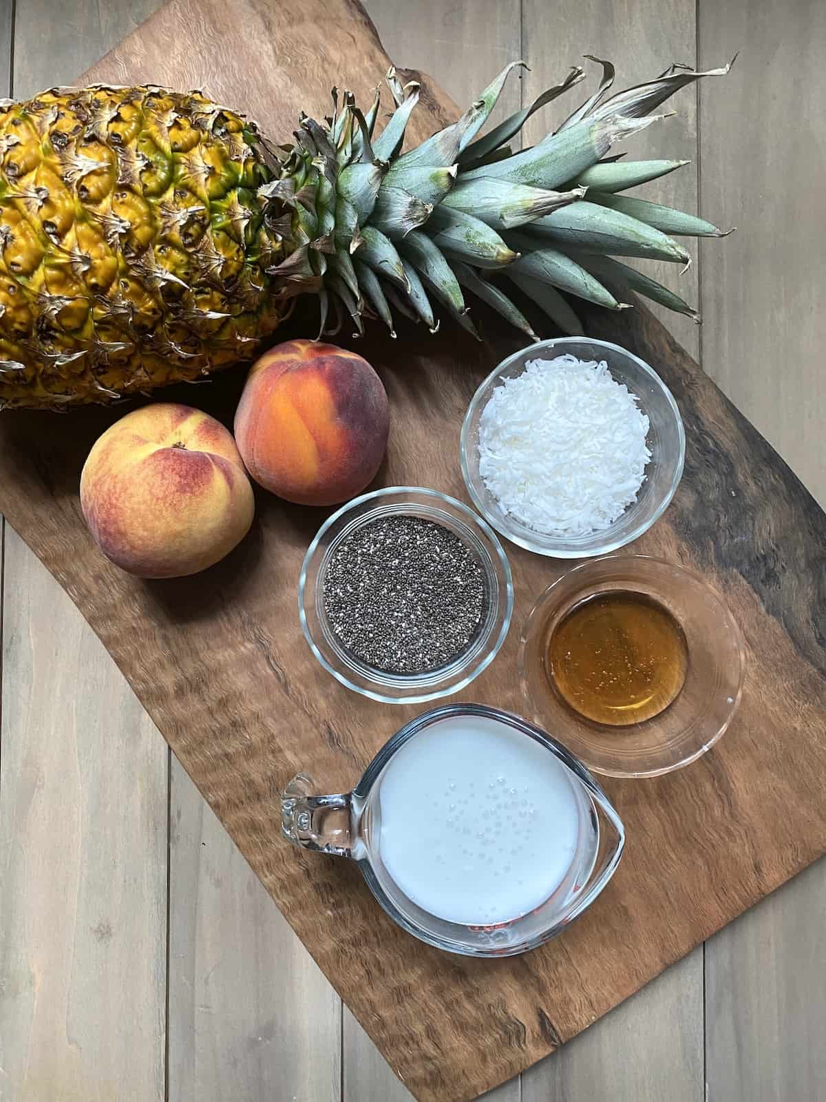 Pineapple, peaches, chia seeds, coconut, honey, and coconut milk on a wood cutting board.