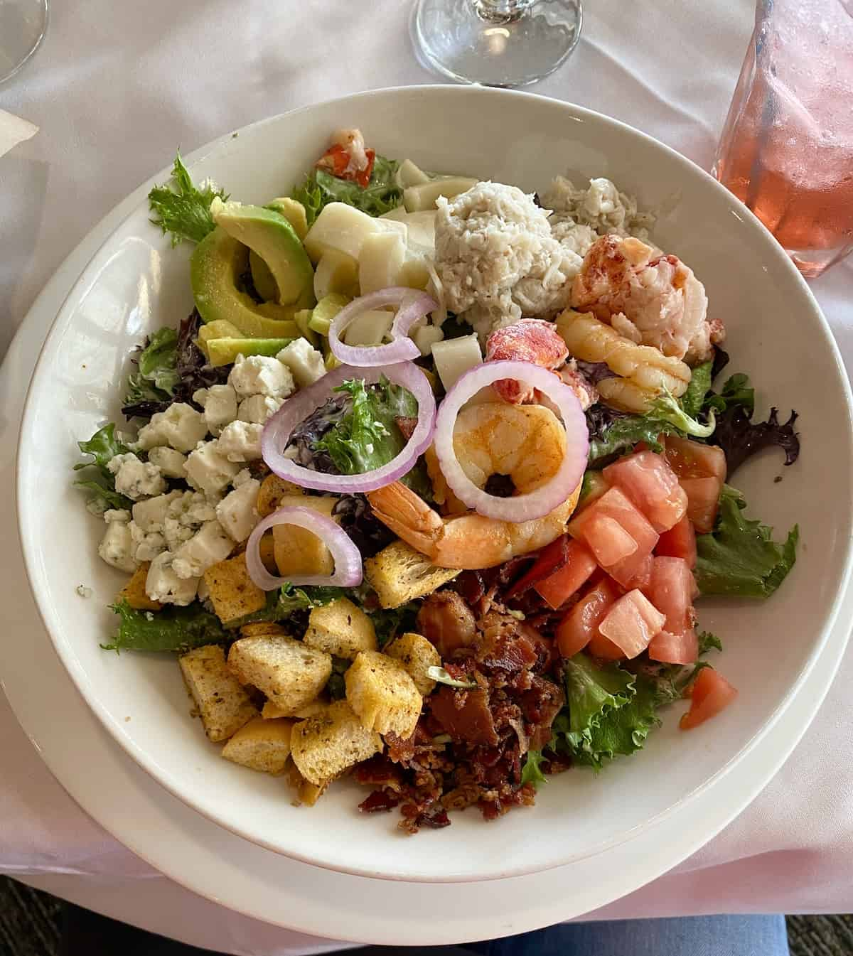 Salad with bacon, cheese, tomatoes, shrimp, crab, lobster, and avocado in a white bowl.