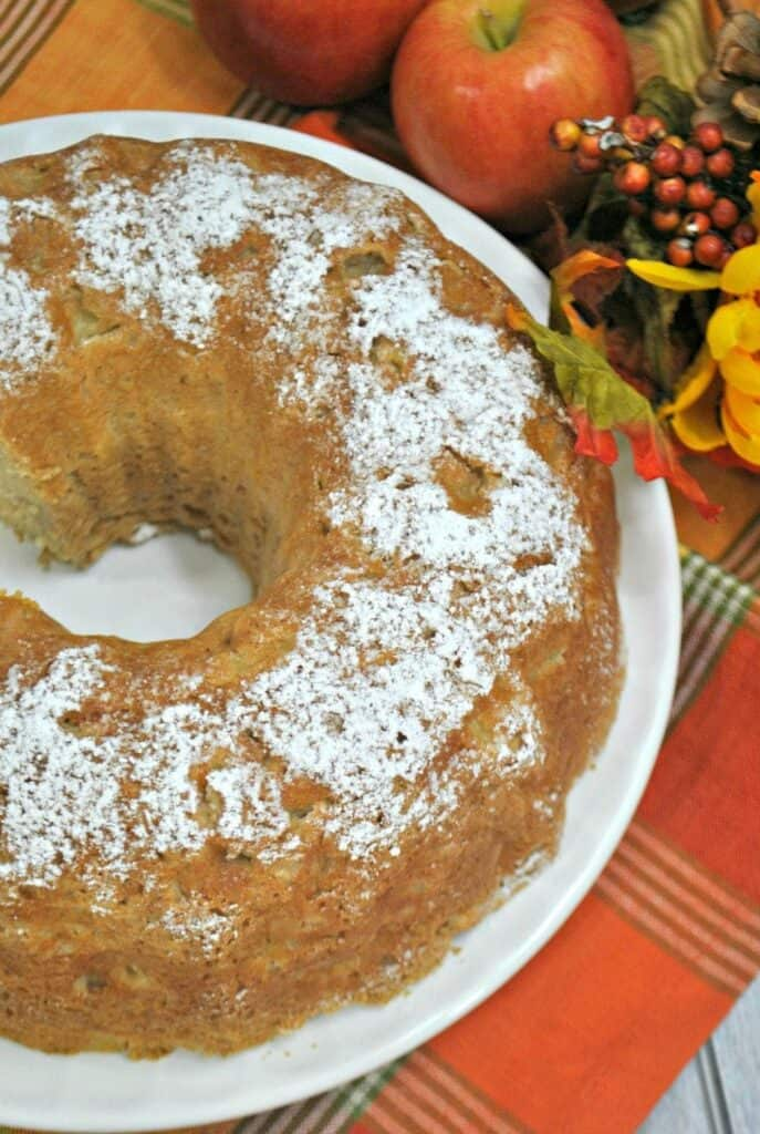 Apple cake with powdered sugar on top on a fall tablecloth.