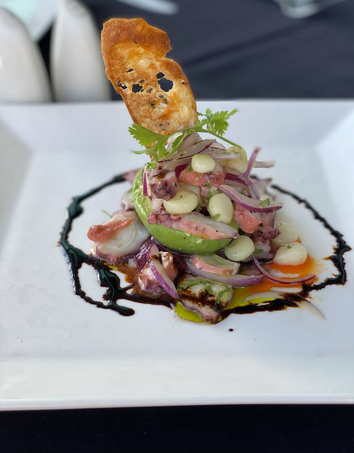 Grilled octopus over yellow pepper potato salad, tomato, corn, and avocado mousse.