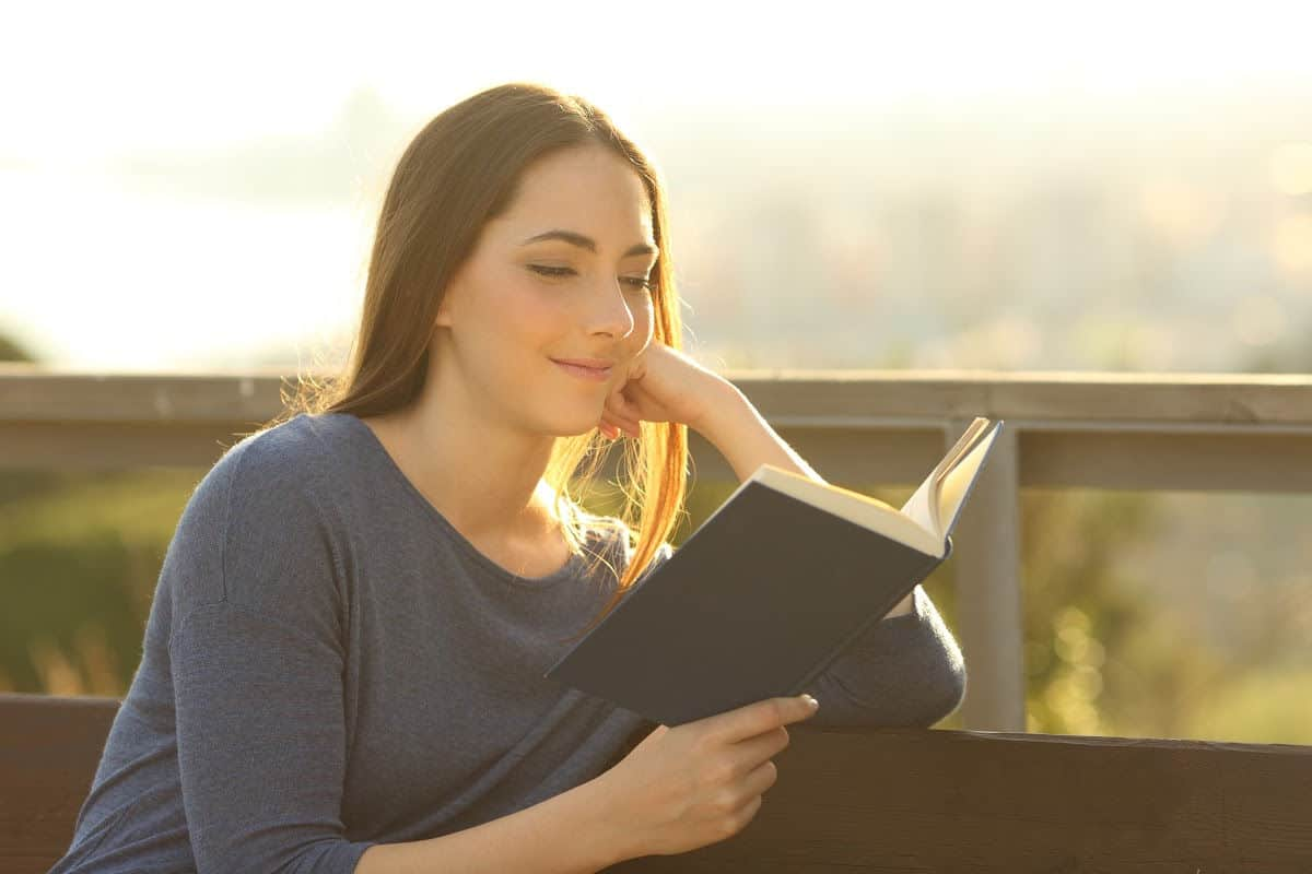 Woman sitting on bench outside reading the Bible.