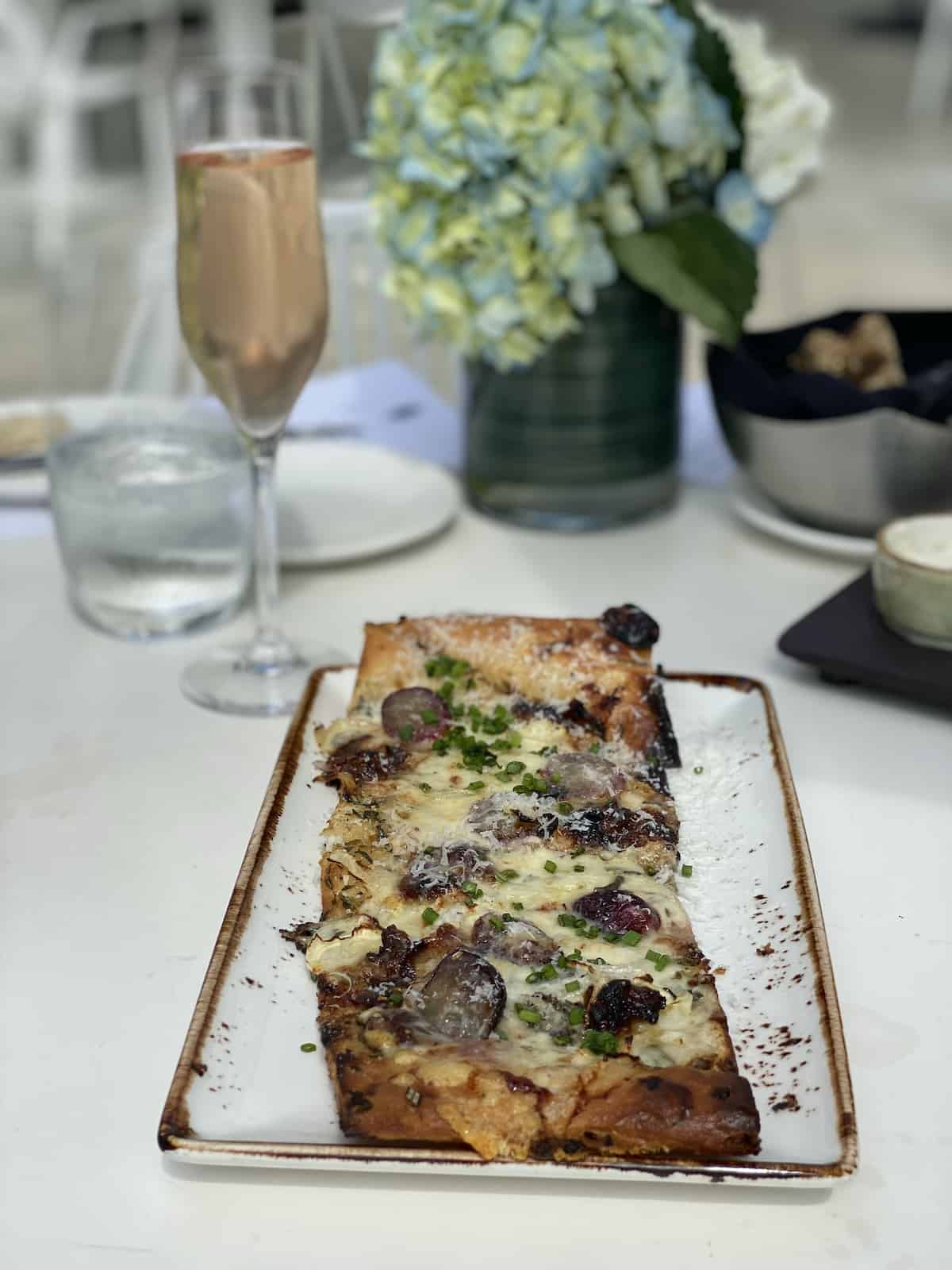 Flatbread with cheese and grapes on white stone platter with glass of Prosecco.