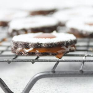 Chocolate cookie with caramel dripping out, topped with powdered sugar set on a wire rack.