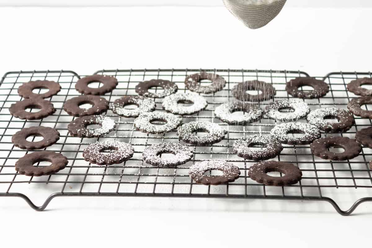 Chocolate cookies being dusted with powdered sugar.