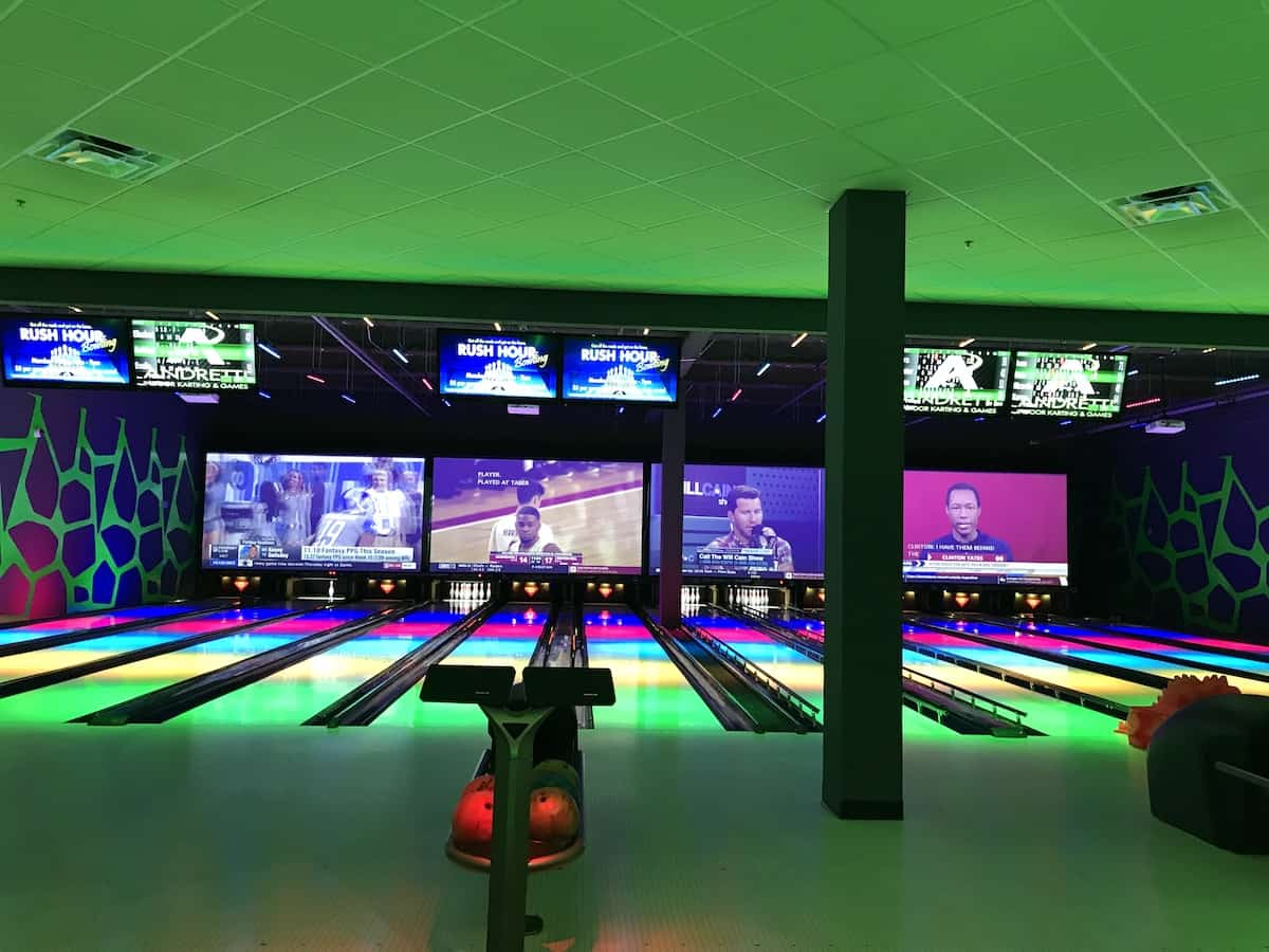 Bowling Alley with green light and LED screens.